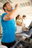 Woman and man biking in the gym, exercising legs doing cardio wo Royalty Free Stock Images