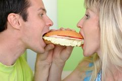 Woman and man bite a sandwich Stock Photo