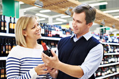 Woman and man with bottle of wine in store Stock Photo