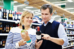 Woman and man with bottle of wine in store. Woman and men with bottle of wine in the store Stock Photography