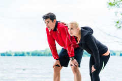 Woman and man at break from running in front of lake Royalty Free Stock Photos