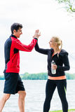 Woman and man at break from running giving each other a high fiv Royalty Free Stock Photos