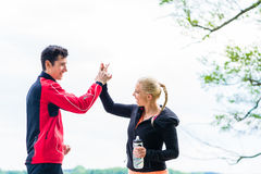 Woman and man at break from running giving each other a high fiv Royalty Free Stock Photography