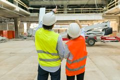 Woman and man builder at a construction site. Building, development, teamwork and people concept. Woman and men builder at a construction site. Building royalty free stock photo