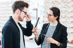 Woman and man buying glasses in optician shop Royalty Free Stock Images