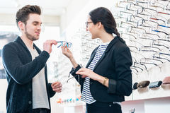 Woman and man buying glasses in optician shop Royalty Free Stock Photography