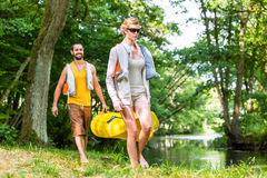 Woman and man carrying together kayak to forest river. Woman and men carrying together kayak to forest river in summer royalty free stock photo