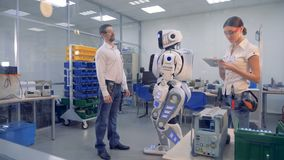 A man orders a robot to turn. Woman and man check robot work, ordering it to make movements