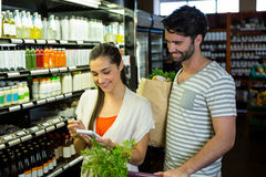 Woman and man checking their notepad while shopping in organic section Stock Photo