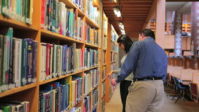 Woman and man choosing book stock footage