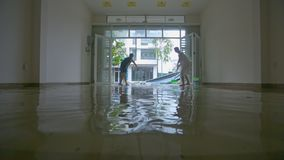 Woman Man Clear out Water from Floor after Devastating Typhoon