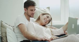 Woman and man closeup using a notebook to order something , they sitting in the sofa in a modern living room wearing stock footage