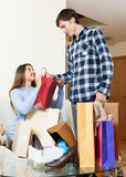 Woman and man with clothes and bags. Woman and men with clothes and bags smiling in home Stock Images