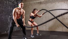 Woman and man couple training together doing battling rope workout. Woman and men training together doing battling rope workout Stock Images
