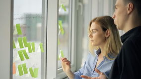 Woman and man are creating working process plan pointing stock video