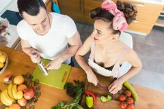 Woman and man cutting vegetables for salad stock images