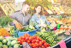 Woman and man are deciding on vegetables. Woman and men are deciding on vegetables in grocery shop Stock Images