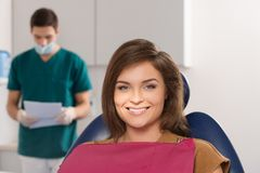 Woman and man dentist surgery. Male dentist reading female patient's card Royalty Free Stock Image