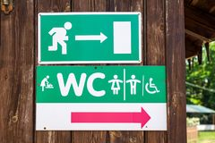 Woman man disabled toilet sign and emergency exit sign royalty free stock image