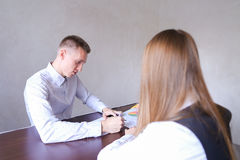 Woman And Man Discuss Work . They Sitting in Office of Wooden Ta Stock Photography