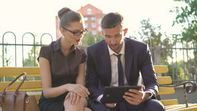 Woman and man discussing issues and working with tablet on the bench. 4K stock video footage