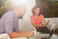 Woman with man discussing over digital tablet Royalty Free Stock Photos