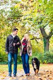 Woman and man with dog having autumn walk. Woman and men with dog having autumn walk on a path covered with foliage Stock Photos