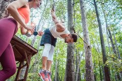 Woman and man doing athletic training in the woods at rings. Woman and men doing athletic training in the woods at rings, she is cheering him Royalty Free Stock Image