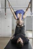 Woman and man doing pilates in cadillac. Stock Photos