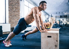 Woman and man doing push ups at gym. Woman and men doing push ups on fit box at gym Stock Photography
