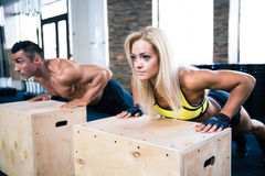 Woman and man doing push ups at gym Stock Photo