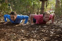 Woman and man doing push ups on a sunny day. In the forest stock photography