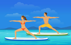 Woman and Man doing Stand Up Paddling Yoga on Paddle Board at Seaside Royalty Free Stock Photo