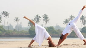 Woman and man doing yoga. An attractive young woman and man doing yoga, Goa, India stock footage