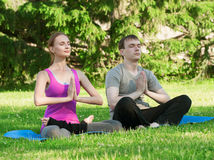 Woman and man doing yoga exercise Stock Photos