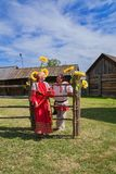 Woman with man, dressed in Russian folk costumes, stands near a village fence. royalty free stock images