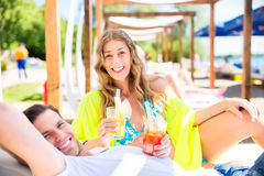 Woman and man with drinks in beach bar Stock Photos