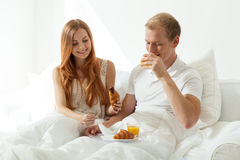 Woman and man eating breakfast in bed Stock Image