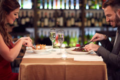 Woman and man eating in restaurant. Woman and men eating good food in restaurant on evening stock photography