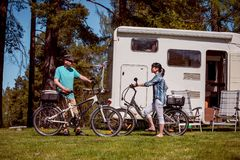 Woman with a man on electric bike resting at the campsite. Royalty Free Stock Images