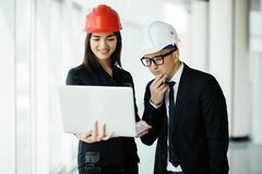 Woman and man entrepreneur and architect in hemlet at business meeting, looking at the laptop on building plans royalty free stock image