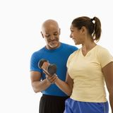 Woman and man exercising. Smiling mid adult multiethnic man assisting mid adult multiethnic woman with dumbbells Royalty Free Stock Images