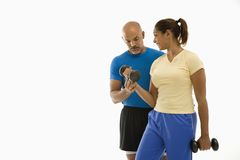 Woman and man exercising. Smiling mid adult multiethnic man assisting mid adult multiethnic woman with dumbbells Stock Photo