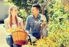 Woman and man with flower basket. Portrait of happy women and men greenhouse workers with their flower basket. Focus on man stock photography
