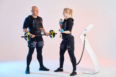 Woman and man in full electrical muscular stimulation suits doing exercise. stock images