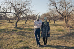 Woman and Man in Gas Masks in the forest. A couple husband and wife, man and woman wearing gas masks surrounded by leafless trees in the forest and blue grey sky Royalty Free Stock Image
