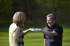 Woman and man golfers congratulating. On golf course Stock Photo