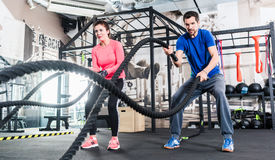 Woman and man in gym functional training with battle rope. Woman and men in gym functional training with battle rope exercising Royalty Free Stock Images