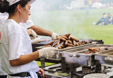 Woman and man handling big sausages and meat Stock Photo