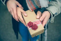 Woman and man hands showing gift box otdoors Stock Images